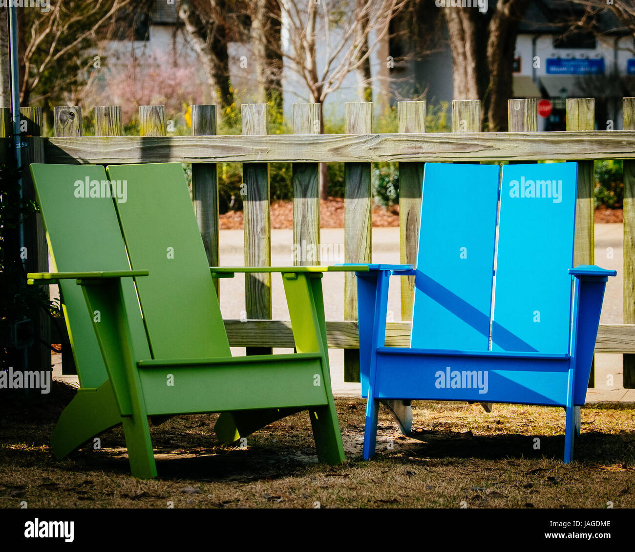 Two Brightly Colored Blue And Green Adirondack Chairs In An