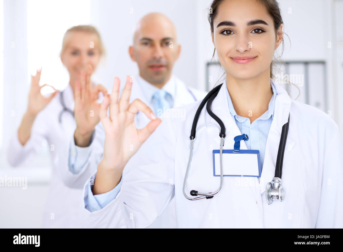 Happy doctor woman with medical staff at the hospital. Thumbs up and Ok sign - Stock Image