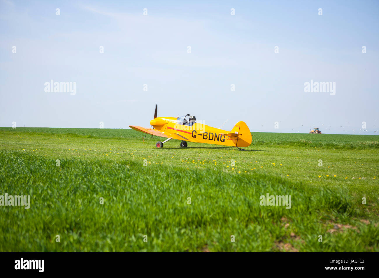 very small yellow aircraft taxiing along rural field ready to take off for flight Stock Photo