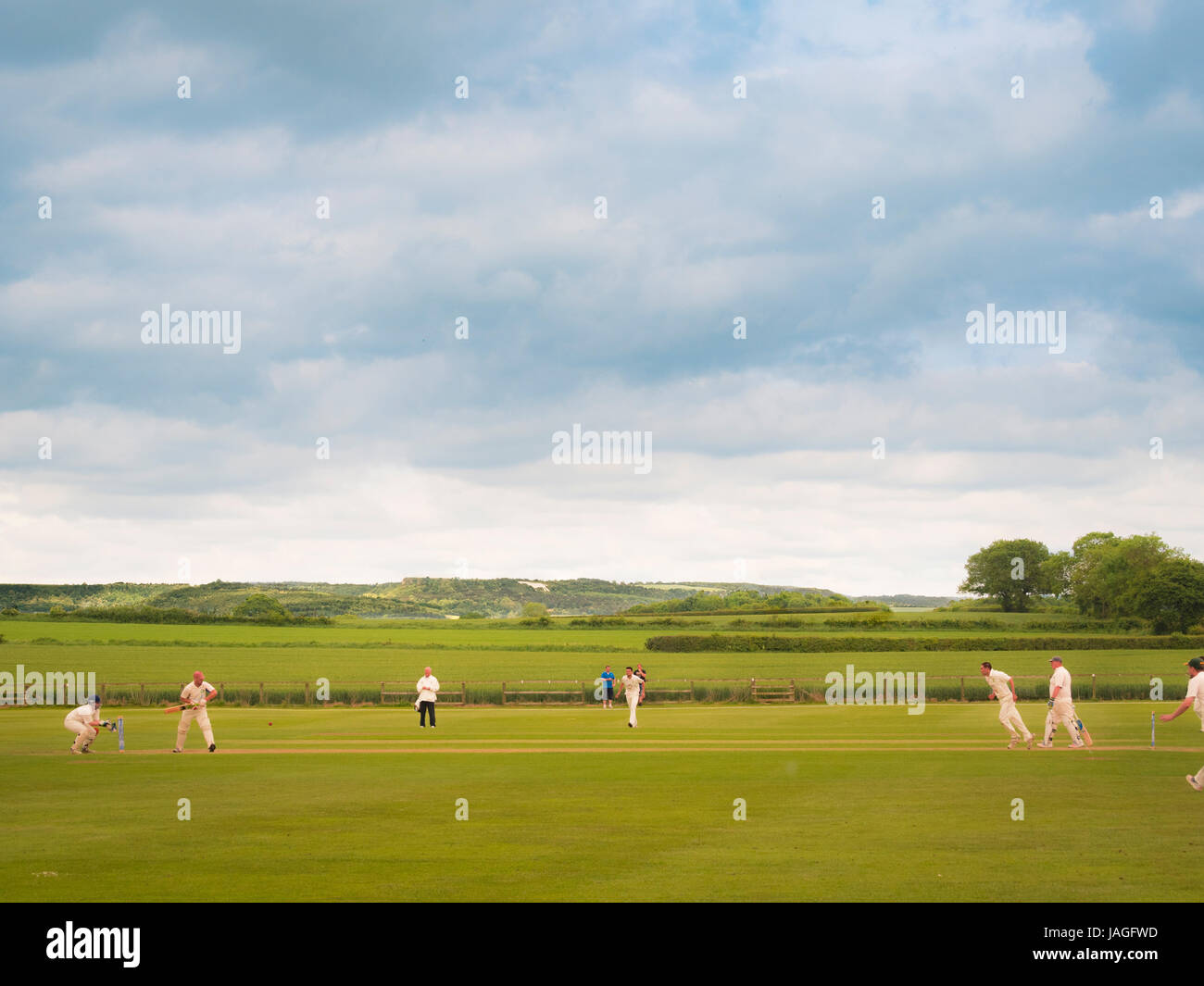 Game of Cricket being played in typical British village of Sessay with the White Horse in the background. - Stock Image