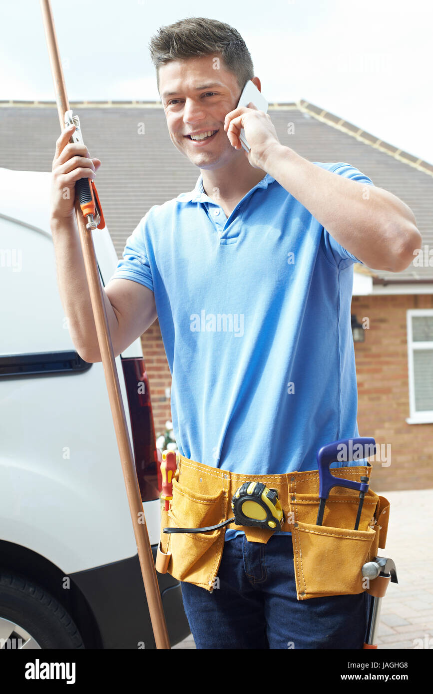 Plumber With Van Talking On Mobile Phone Outside House - Stock Image