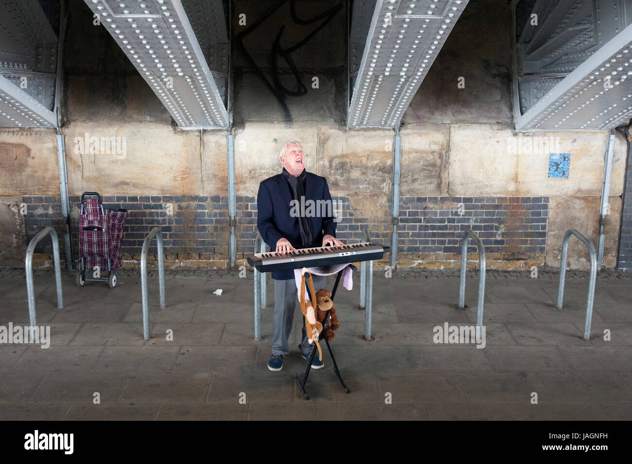London, United Kingdom, 6 may 2017: elderly man sings at electric piano under blackfriars bridge in london - Stock Image