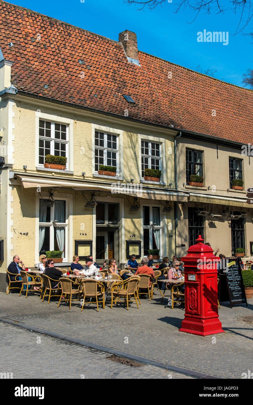 Tourists seated at tables in an outdoor cafe, Bruges, West Flanders, Belgium - Stock Image