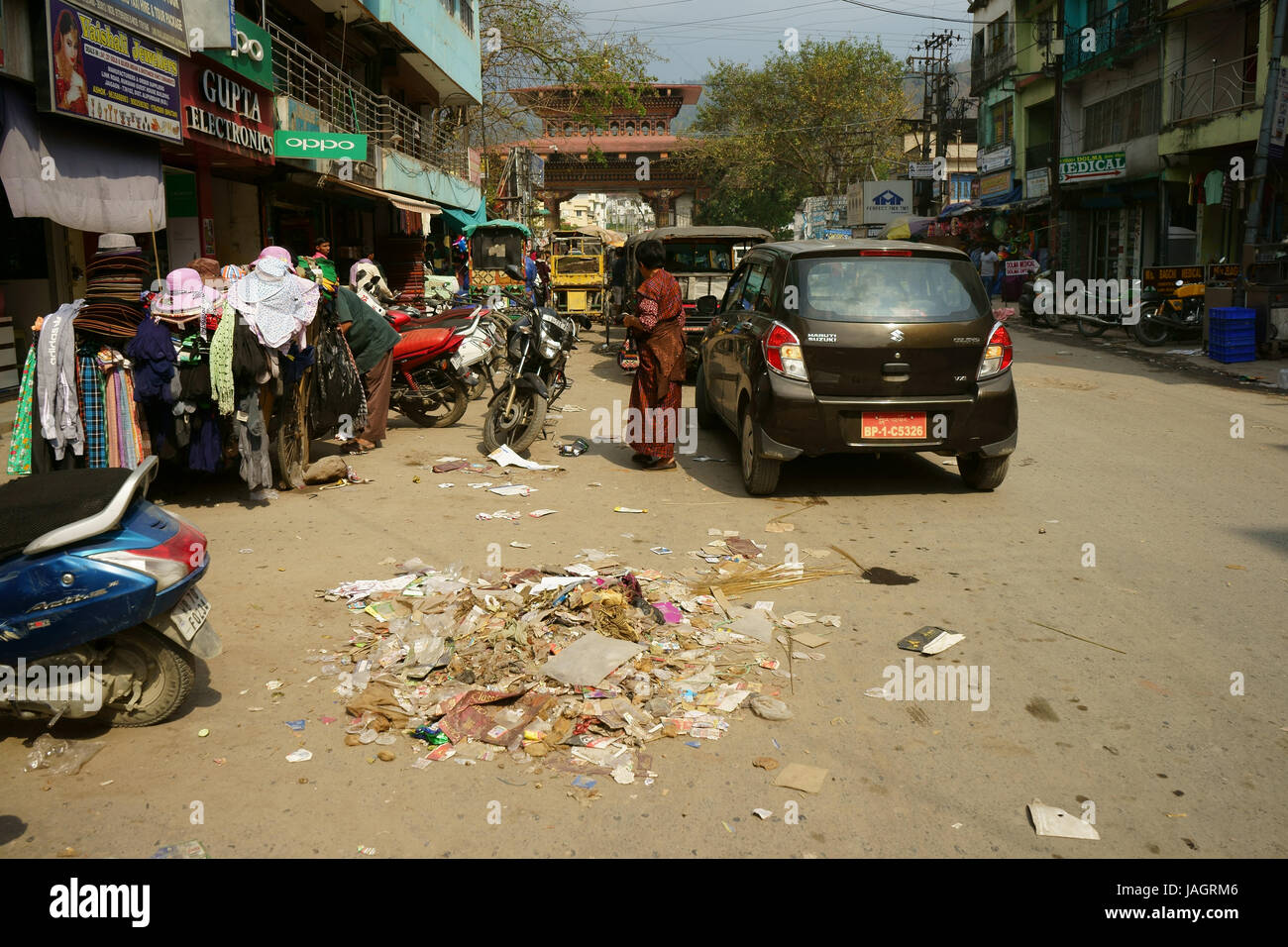 Street littered with garbage at Phuentsholing with border gate to Bhutan in back, WEest Bengal, Inmdia - Stock Image
