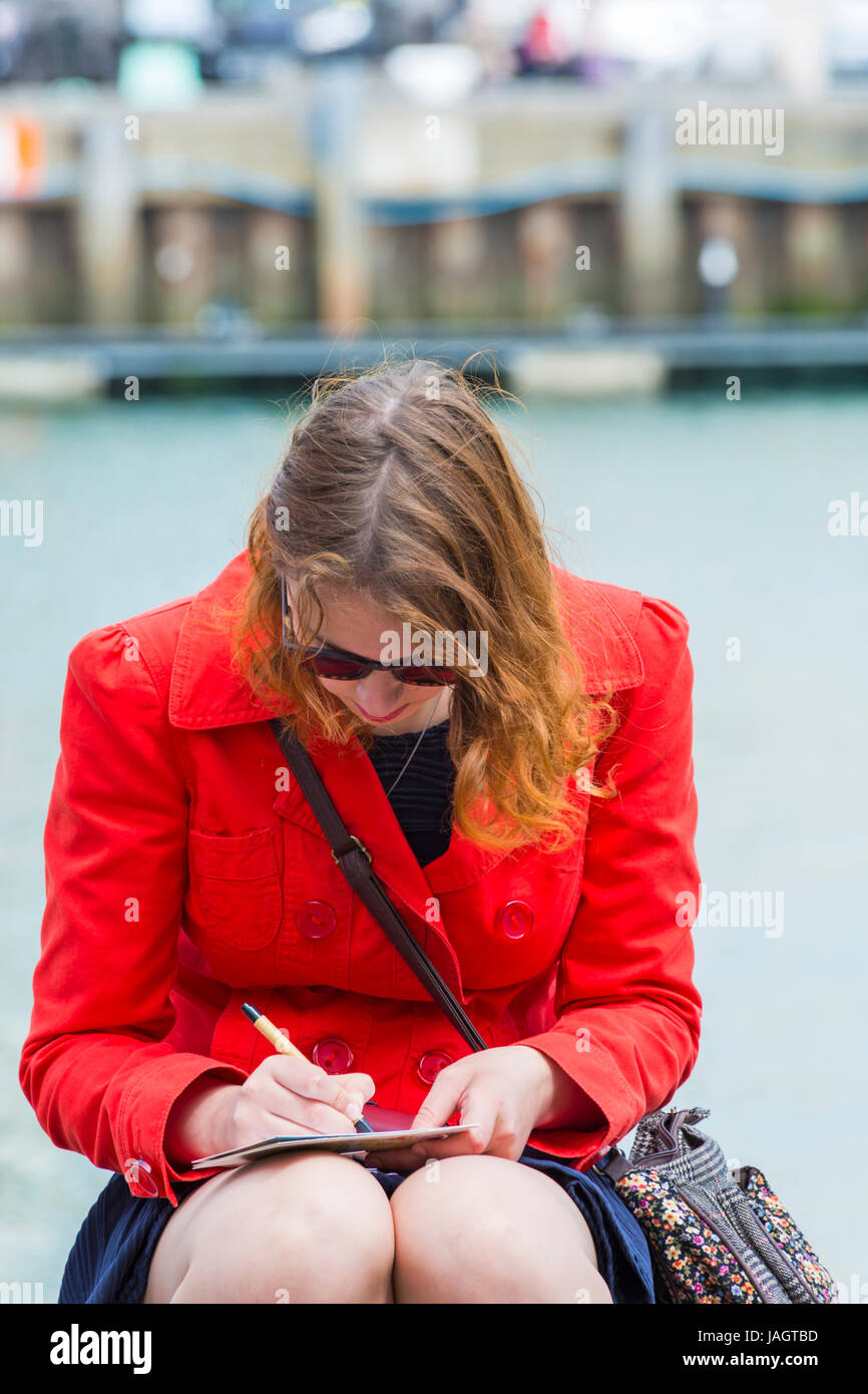 Woman writing postcards sitting on harbourside at Weymouth, Dorset in June - Stock Image