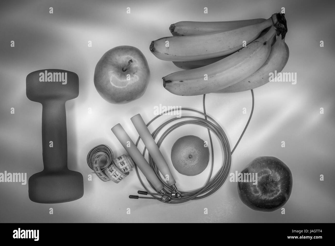 healthy eating concept. Dumbbell, rope, bananas, orange, measuring tape waist, oranges, red apple, green apple, - Stock Image