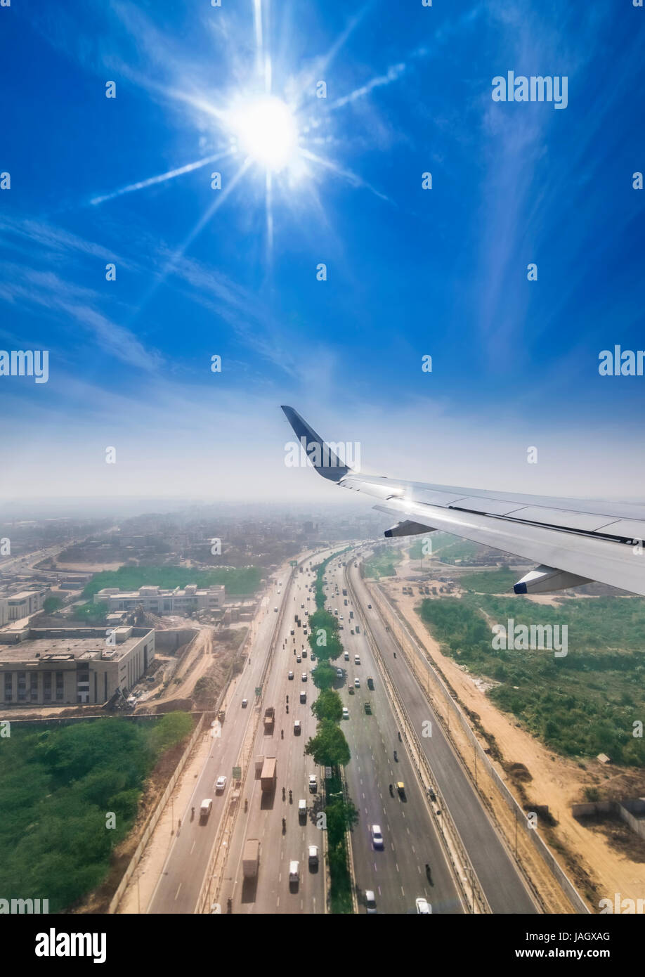 View through the window of a passenger plane flying above Delhi Gurgaon highway, taken just a minute before landing - Stock Image