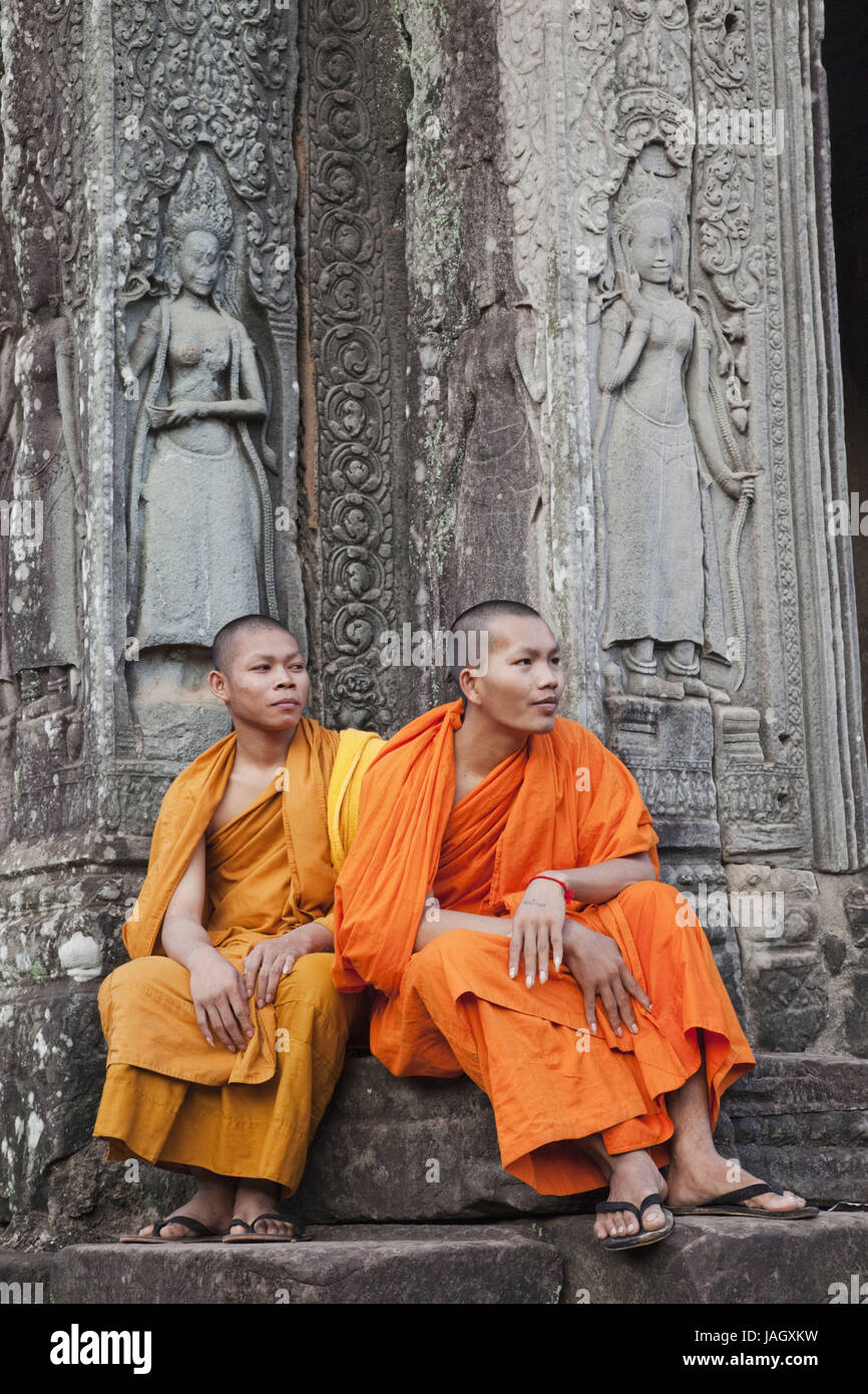 Cambodia,Siem Reap,Angkor Thom,Bayon temple,monks sit before relief with representation of Apsara dancers, - Stock Image