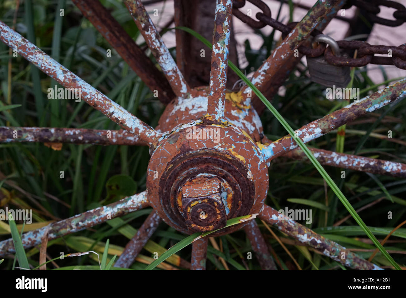 Old Weathered Wagen Wheel With Rust And Yellow Blue Spots - Stock Image