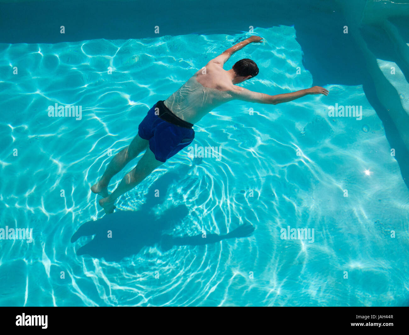 Motionless body of swimmer (drowned?), floating in swimming