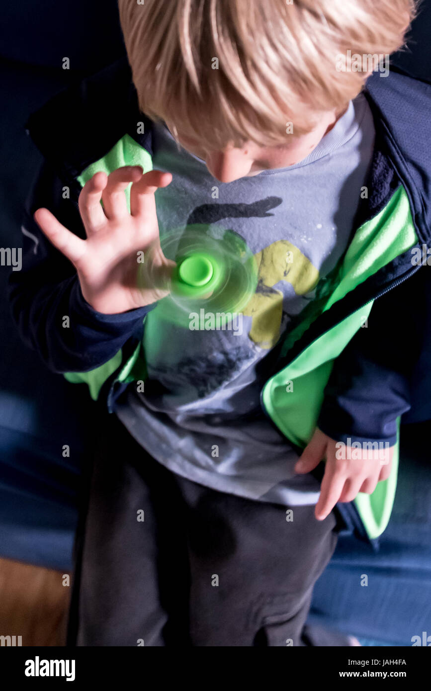 A boy plays with a fidget spinner at home, the controversial stress relief toy found to help some antsy or autistic - Stock Image