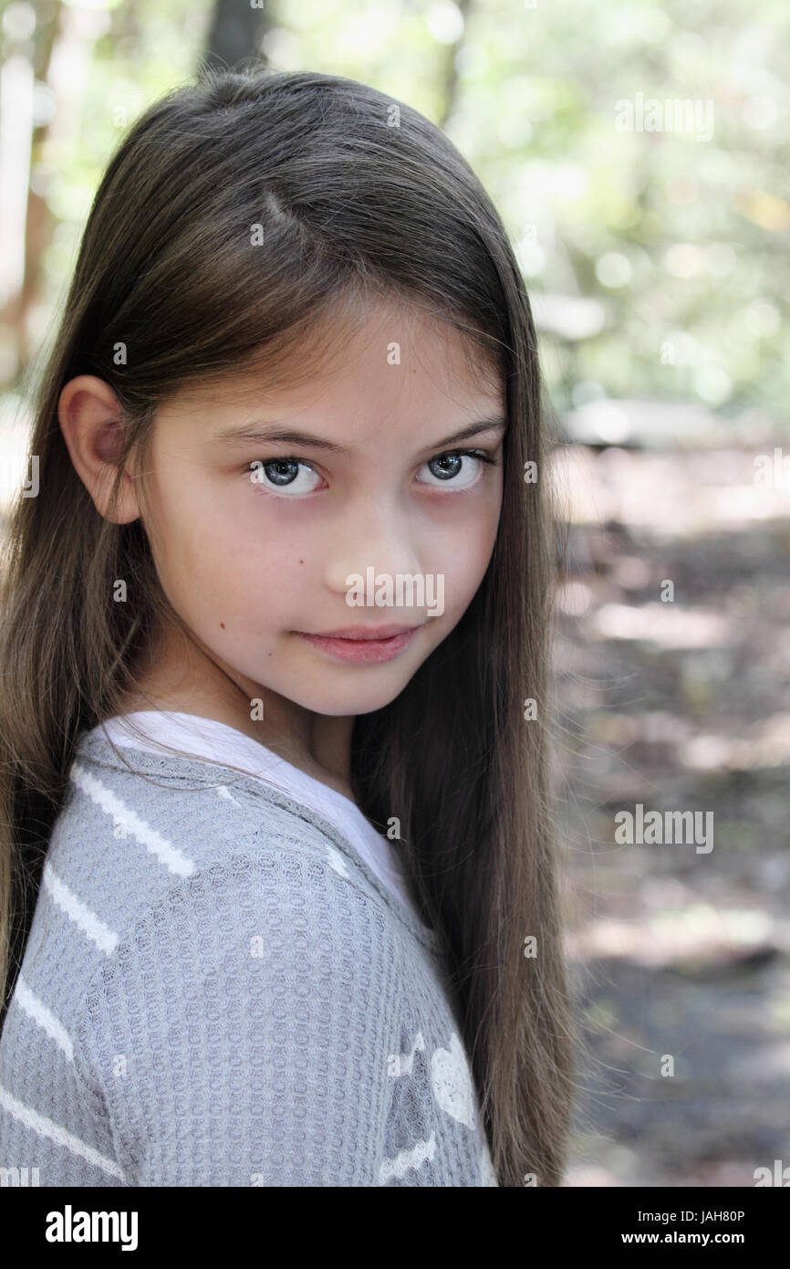 Young pre-teen kid with long hair looking directly into the camera. - Stock Image