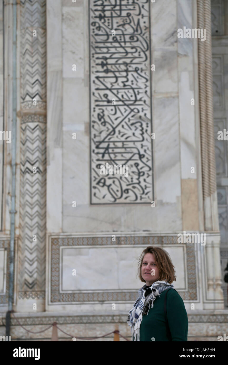 tourist in front of the scriptures on the Mausoleum of Taj Mahal, Agra, State of Uttar Pradesh, India - Stock Image