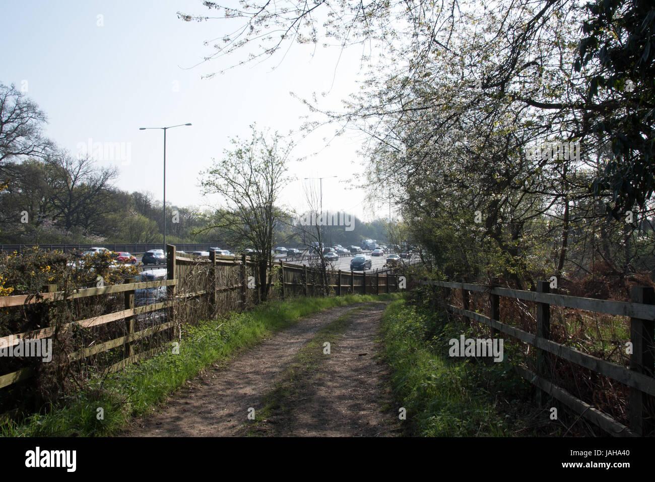 Farm track alongside the London's Orbital Motorway, the M25. - Stock Image
