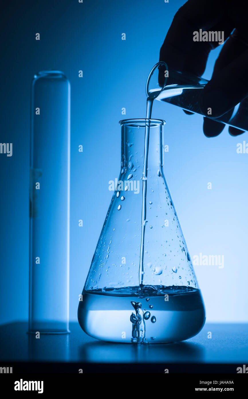 Hand Sihouette with test tube fills a Erlmeyer-piston with a blue tinted studio background. - Stock Image