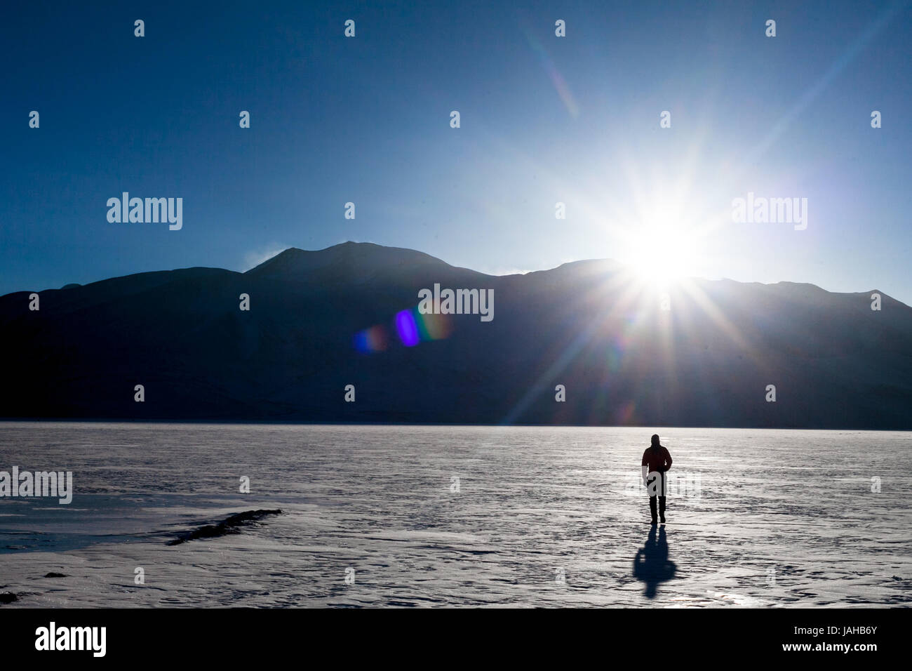 The Tsomoiriri lake in Ladakh completely freezes over during the winters. Here you see a man walking over the surface - Stock Image