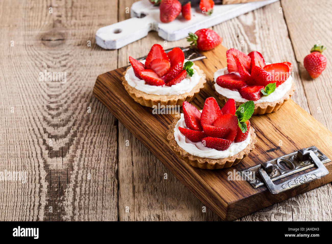 Strawberry shortcake pies on rustic wooden table,  perfect party individual fresh fruit dessert - Stock Image