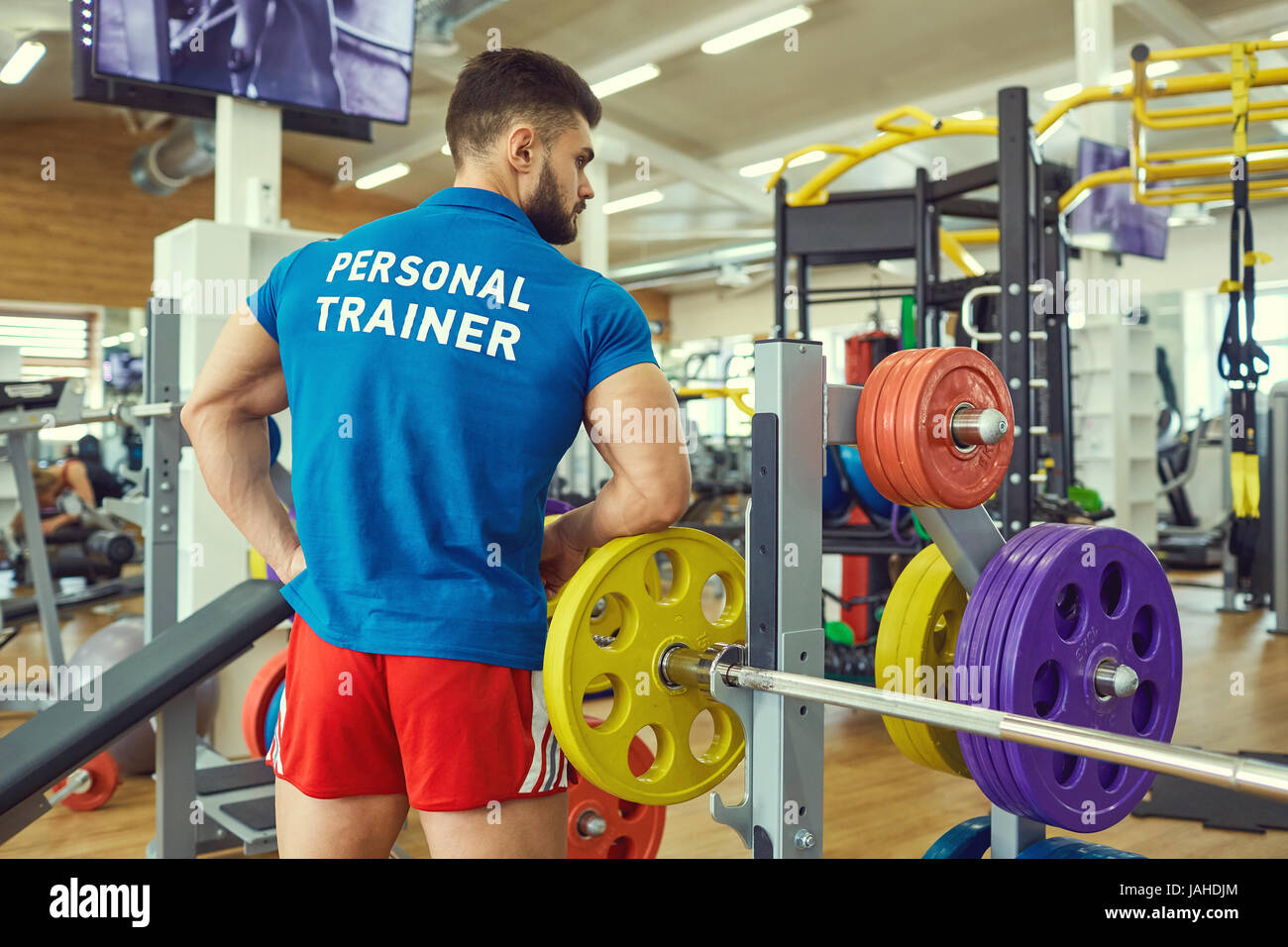 Personal trainer in the sports club. - Stock Image
