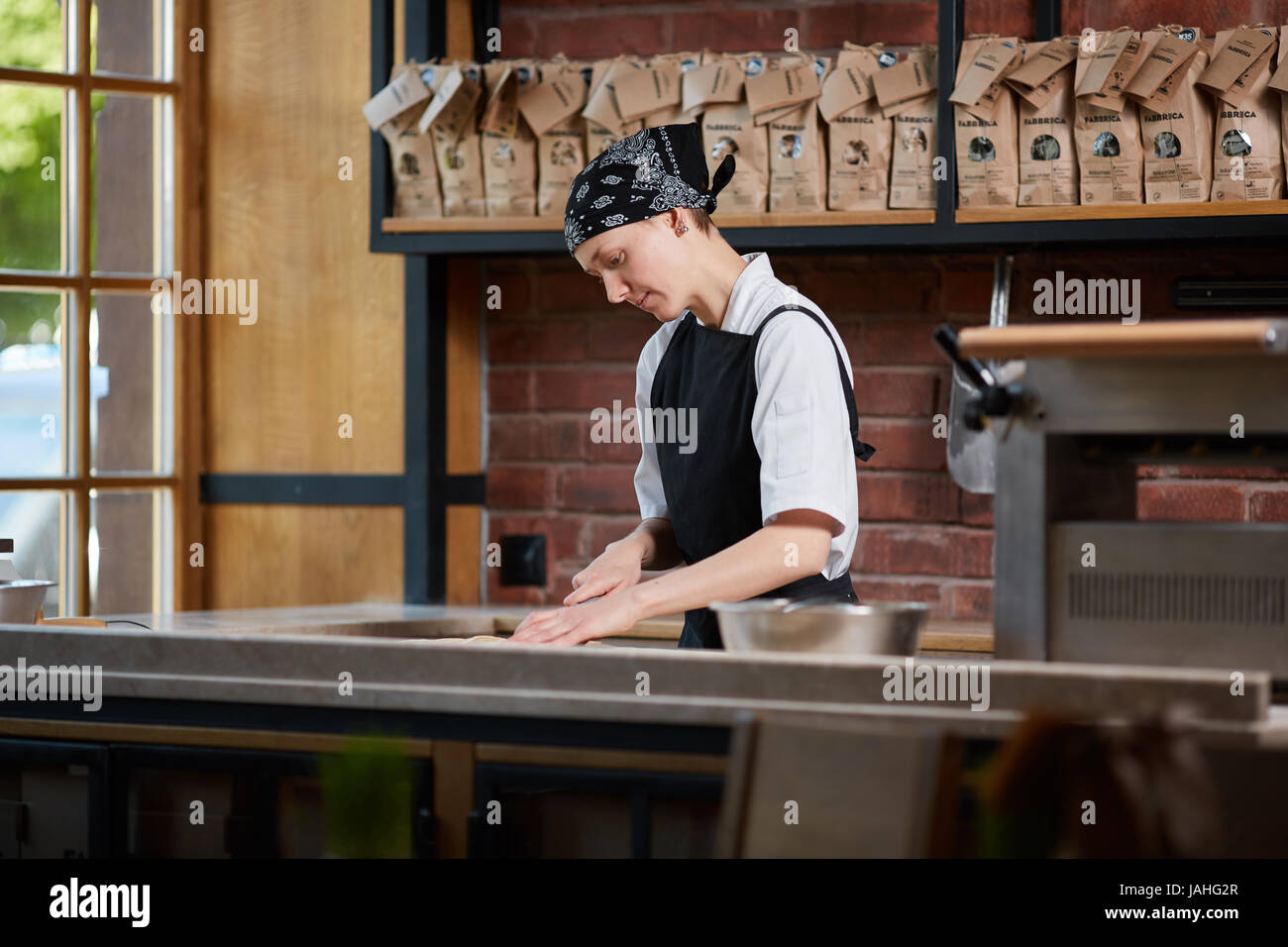Woman slicing noodles in cafe - Stock Image