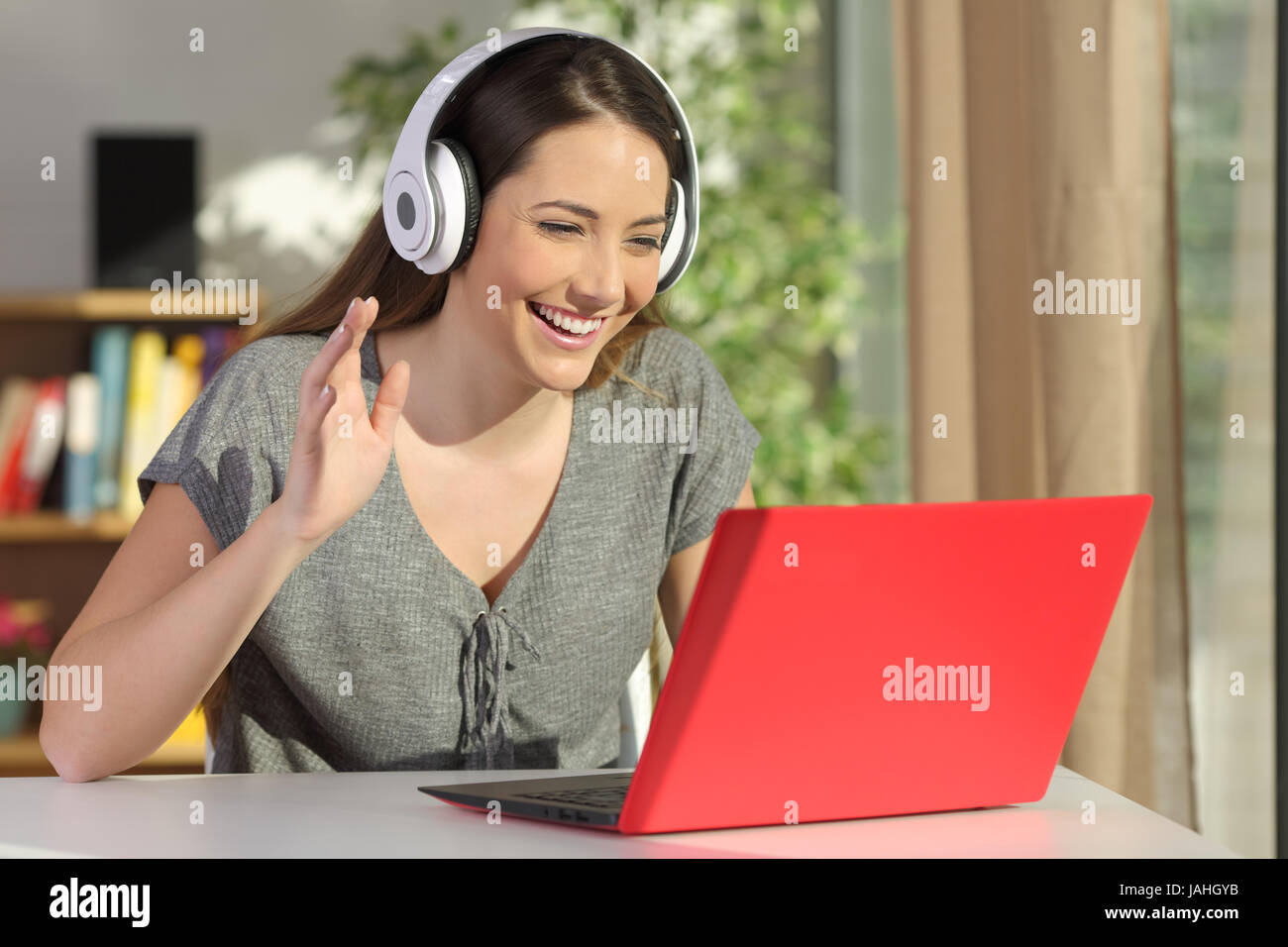 Happy woman wearing headphones greeting during a video conference on happy woman wearing headphones greeting during a video conference on line with a red laptop sitting in a table in the living room m4hsunfo