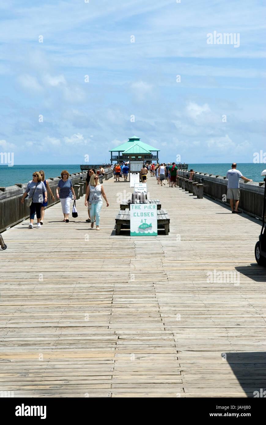 Stock photo of tourists walking along Folly Beach Fishing Pier in