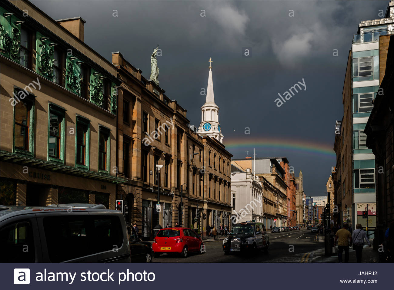 A late-afternoon rainbow arches over Glasgow's Merchant City, whose 18th-century warehouses once bustled with - Stock Image