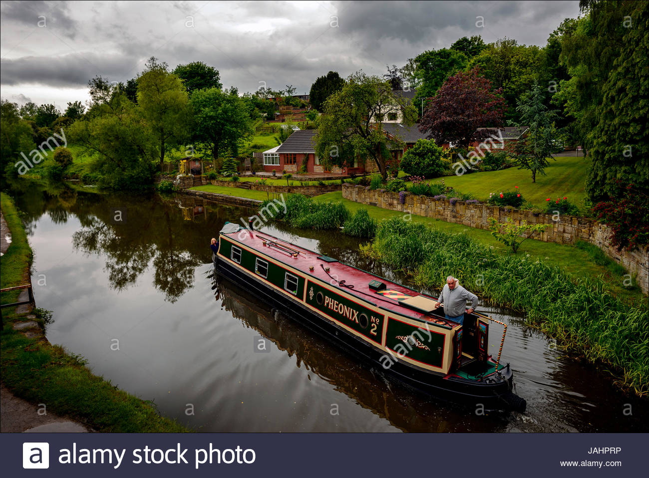 Near Wigan, a pleasure boat cruises the 127 mile long Leeds and Liverpool canal, the longest in northern England. - Stock Image