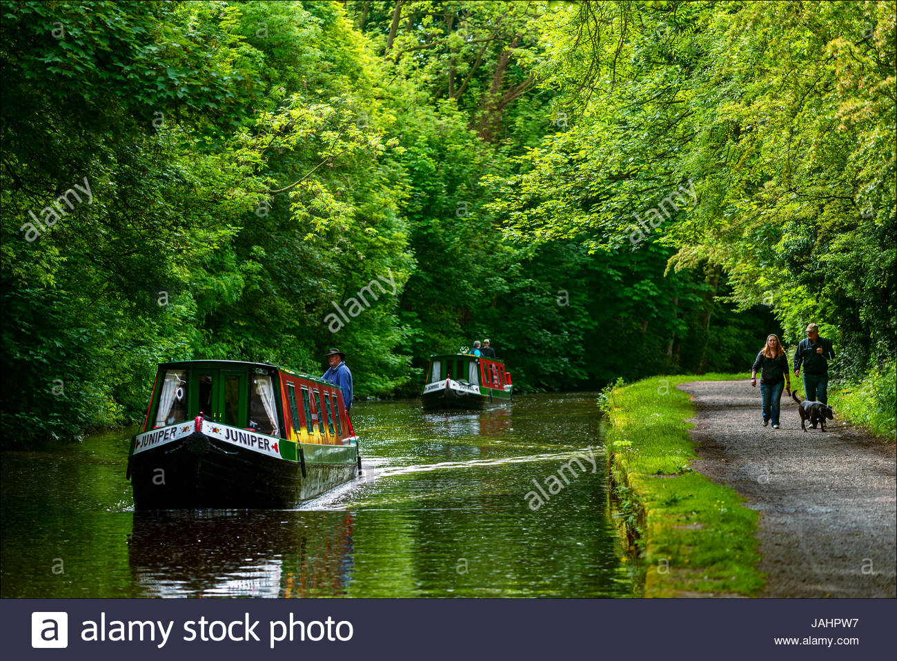 Two canal boats filled with tourists approach the Bingley Five Rise Lock staircase on the Leeds and Liverpool Cana - Stock Image
