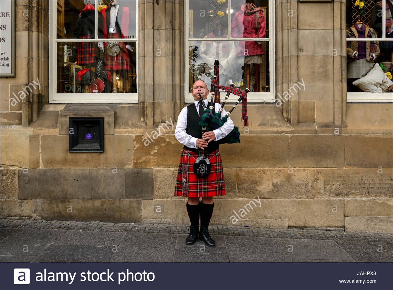 A Scottish bagpiper in traditional kilt entertains passersby, many of whom are tourists, on the Royal Mile in Edinburgh. - Stock Image