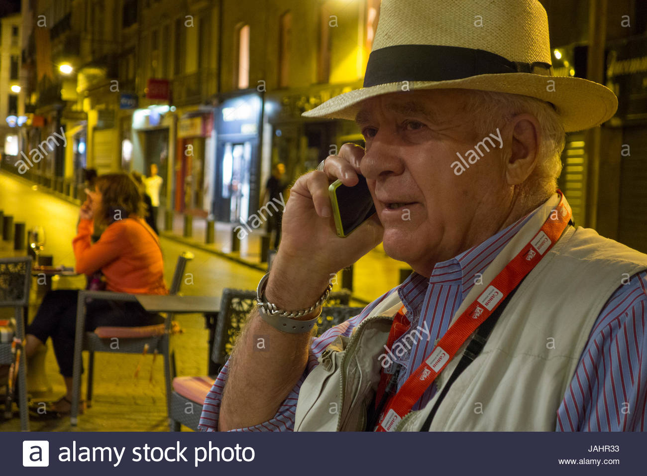 Photographer William Albert Allard, talking on a cellphone, in the streets of Perpignan, France. - Stock Image