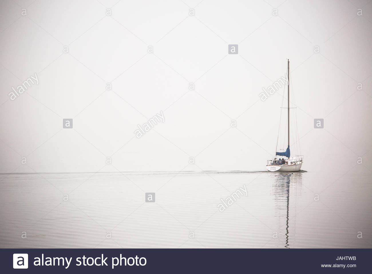 A lone sailboat motors through morning fog on the Occoquan River, near the Potomac River. - Stock Image