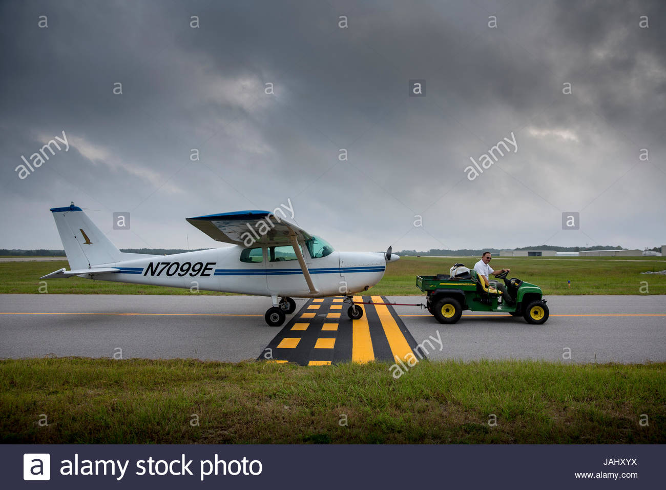A broken down airplane being towed back to hangar. - Stock Image
