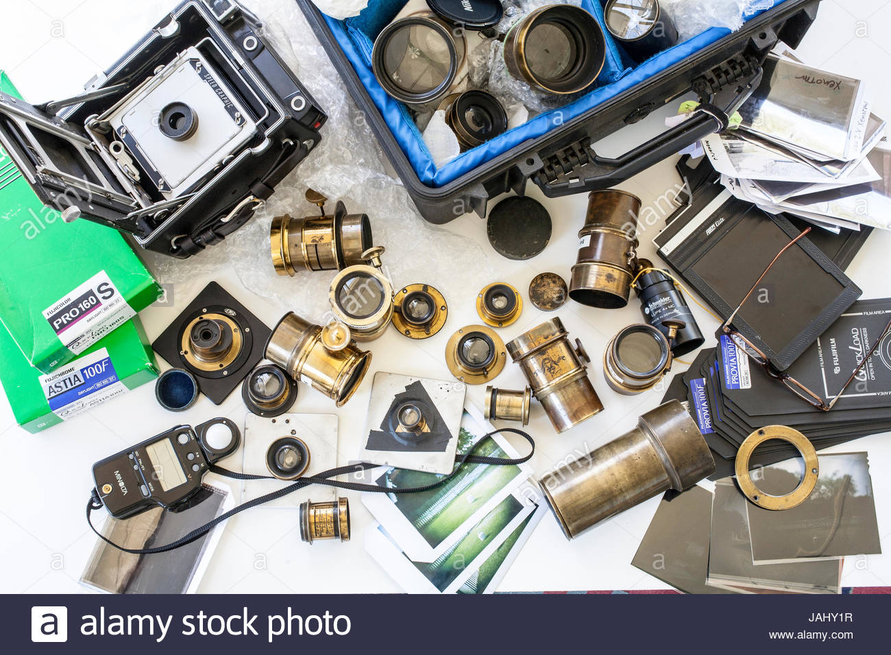 Large format photographic equipment, including film and vintage lenses. - Stock Image