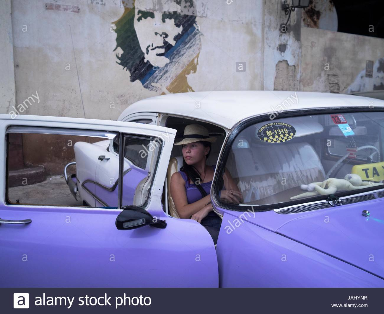 A woman sits in a taxi parked by a wall with a mural of Che Guevara. - Stock Image