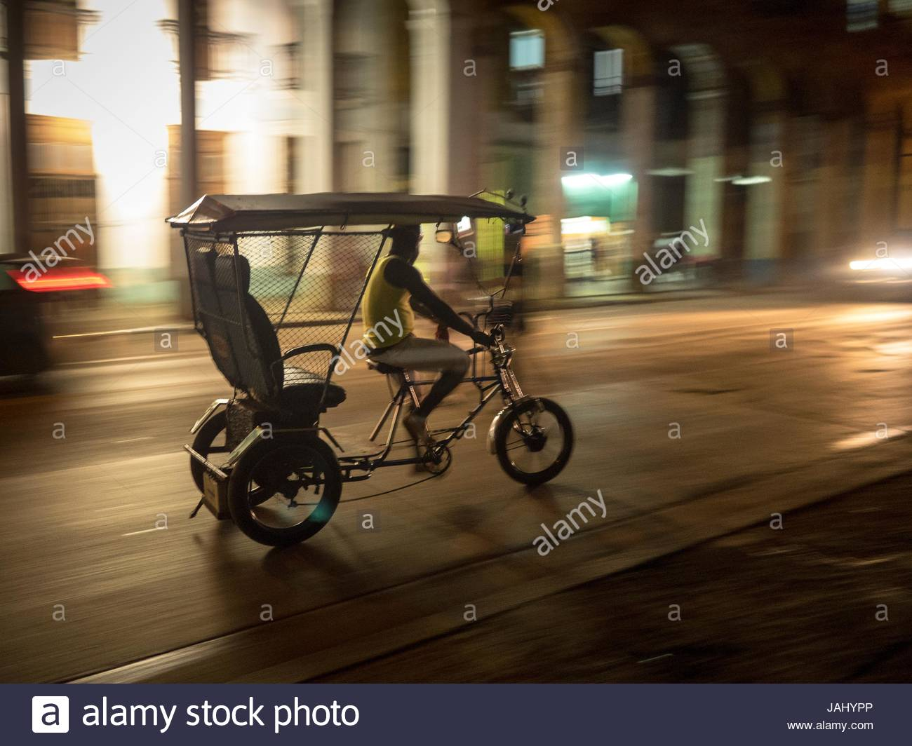 A bicycle cab moves along the Avenida de Belgica at night. - Stock Image