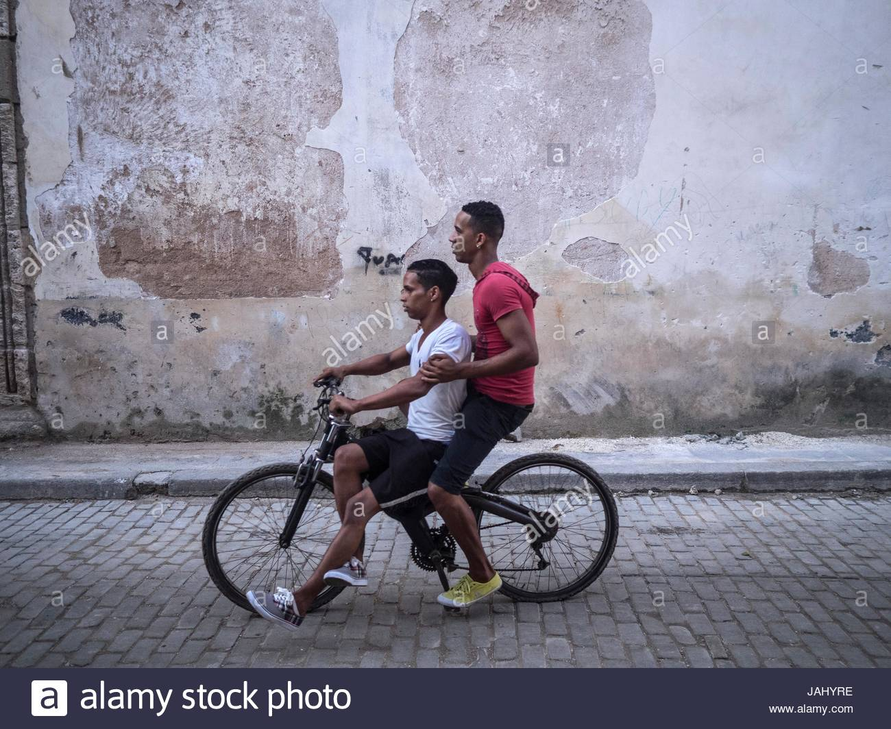 Young men double up on a bicycle in Calle Teniente Rey. - Stock Image