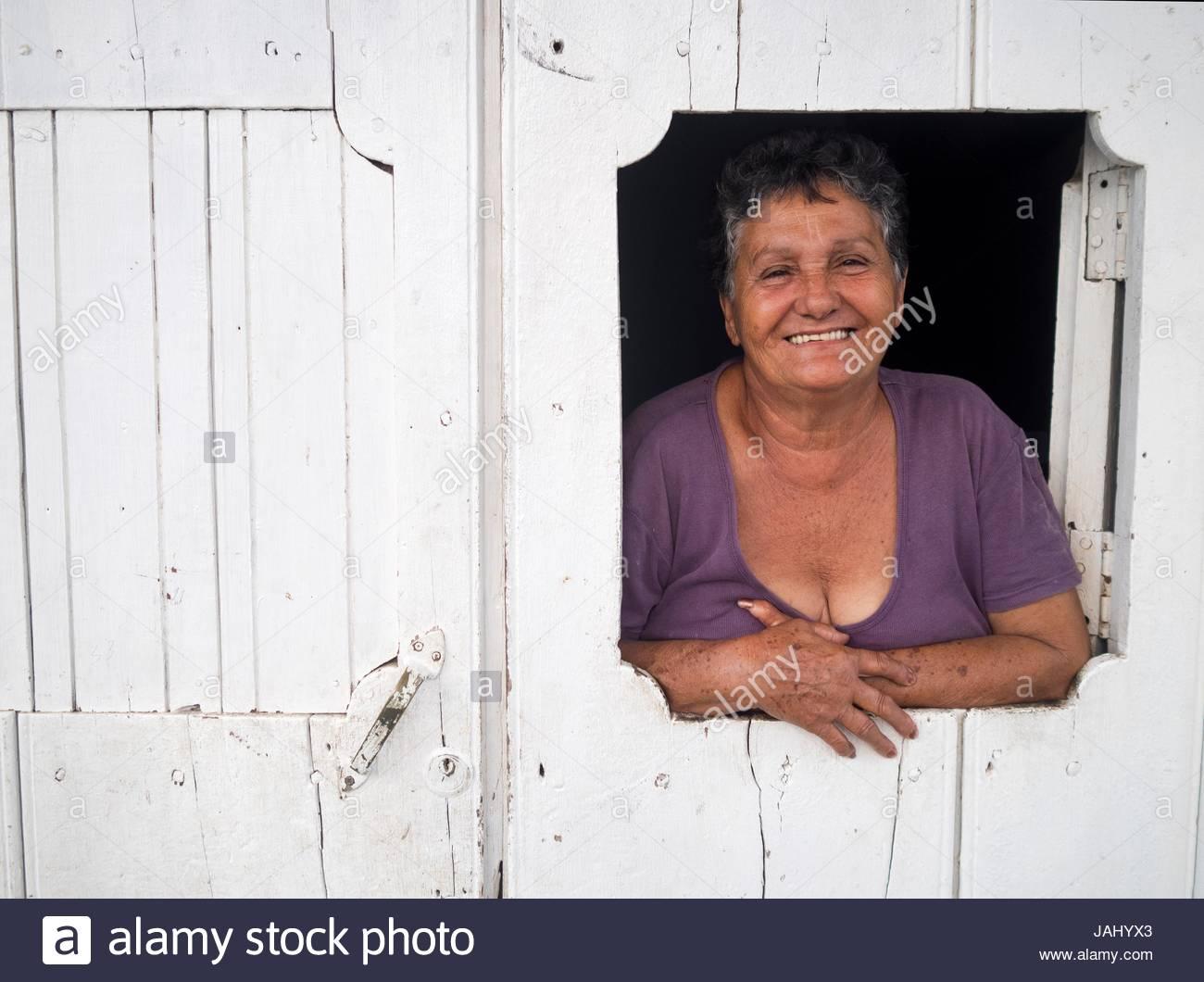 Portrait of a woman looking through a window in a door in Viales, Cuba. - Stock Image