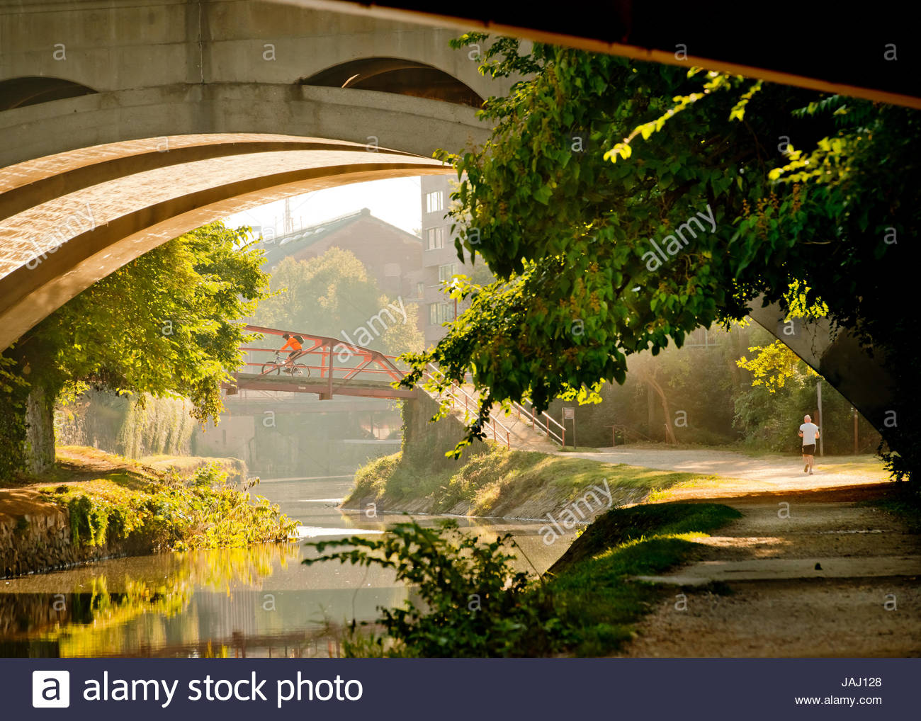 A man runs along the towpath of the C & O Canal in Georgetown. - Stock Image