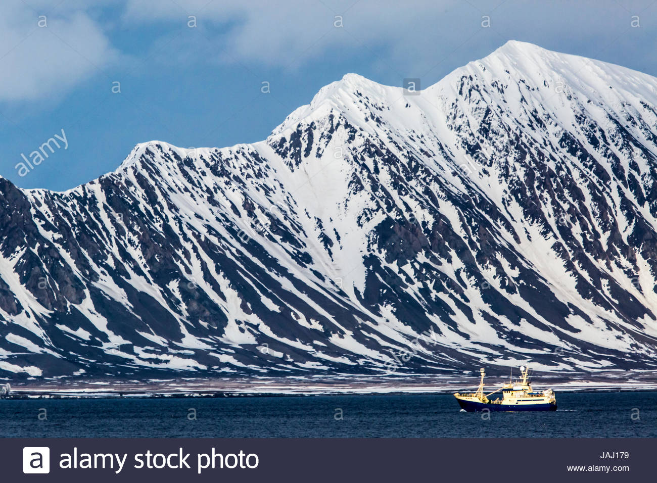 A ship, and the coast of Spitsbergen Island near the mouth of Isfjord. - Stock Image