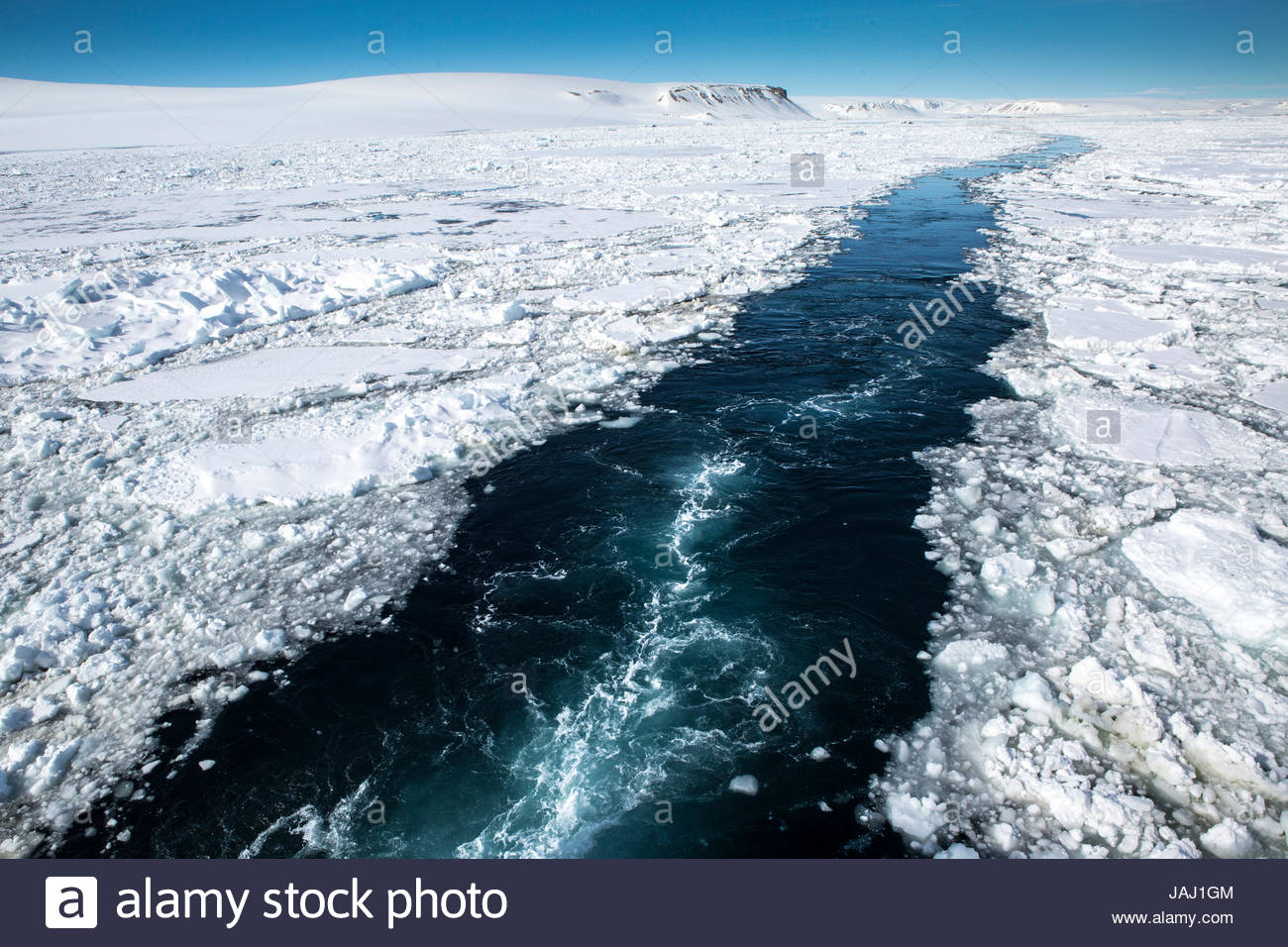 The wake of the expedition cruise ship National Geographic Explorer through the pack ice in Hinlopenstretet. - Stock Image