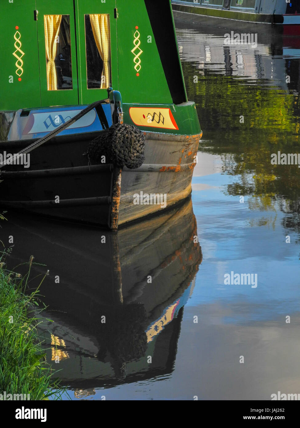 A moored canal barge and reflection in the water of the Shropshire Union Canal on a summer evening walk near Audlem, - Stock Image
