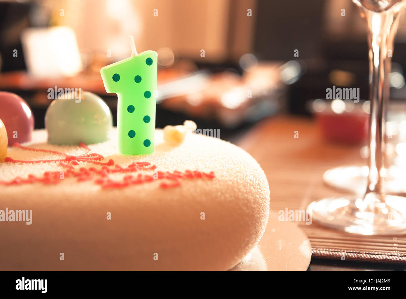 Happy birthday cake for children party decorated with one candle and sweet balloons in honour of first birthday - Stock Image