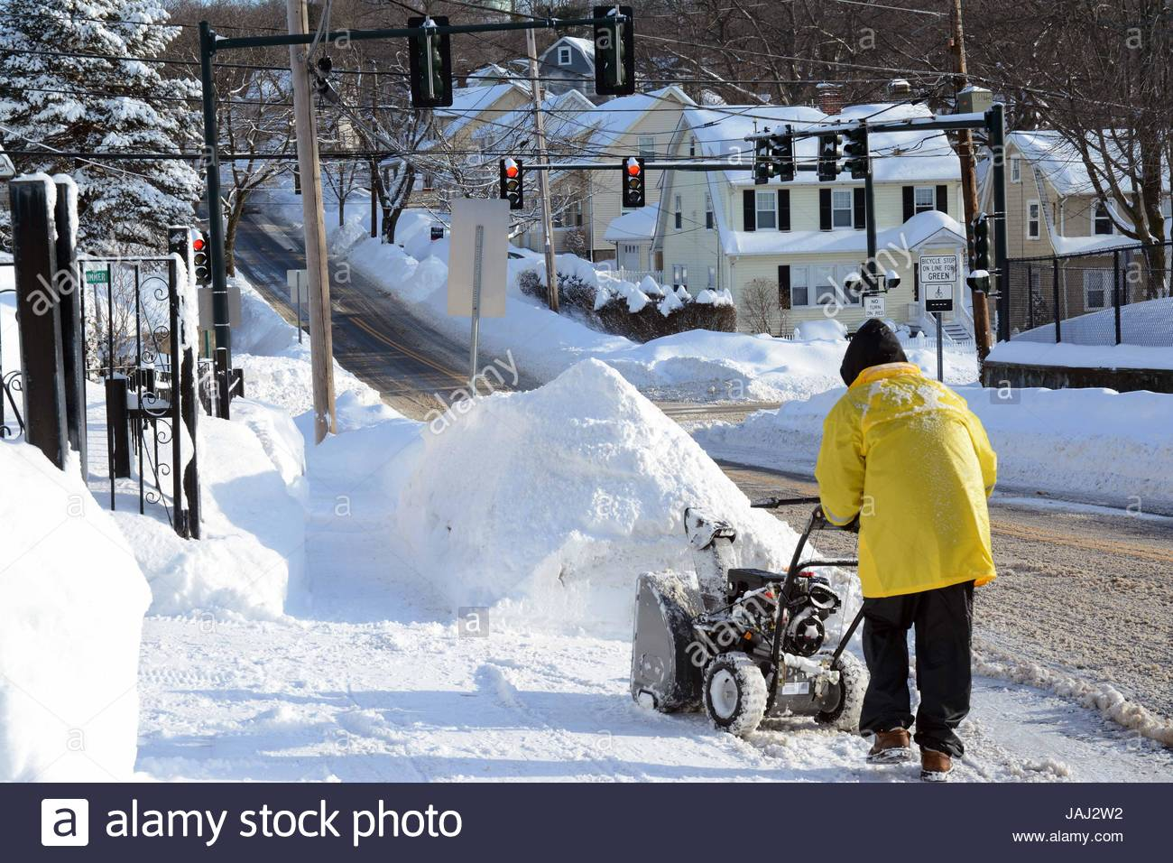 A person with a snow blower cleaning up after a record storm in the Boston area. - Stock Image