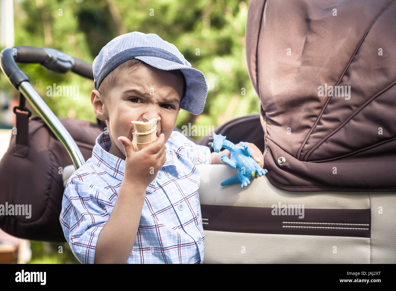 Big brother watching and guarding his junior brother in perambulator while walking in summer park and eating ice - Stock Image