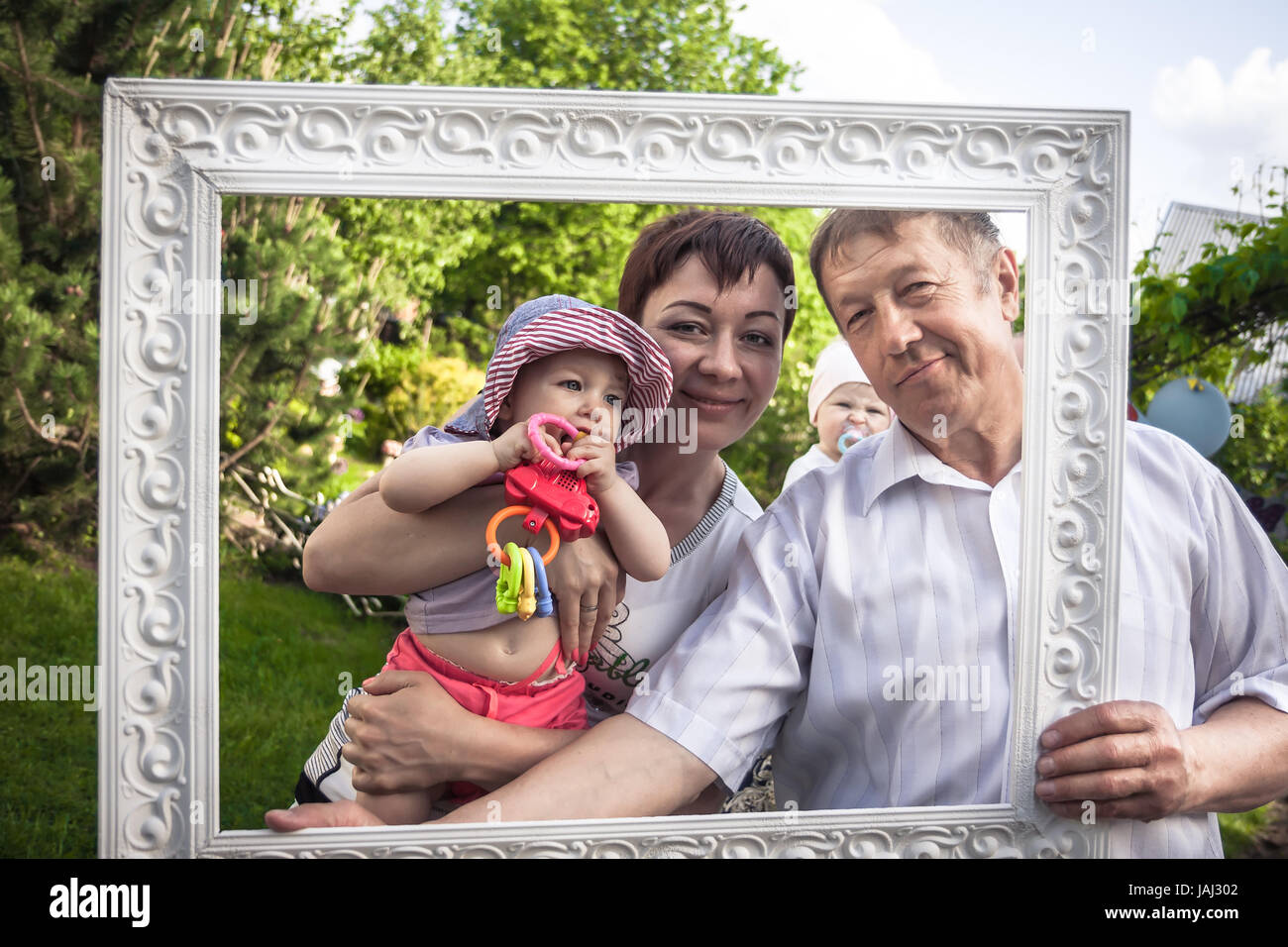 Happy family portrait of cheerful grandfather with his daughter and grandchild during outdoors party - Stock Image