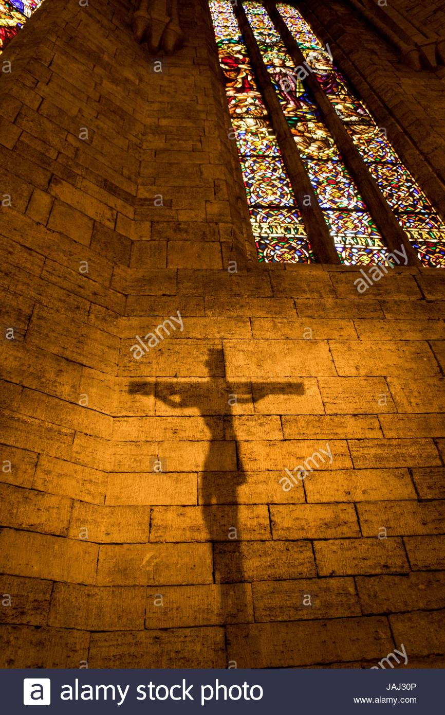 The shadow of a crucifix is projected on the wall of the church of Santa Maria de Porqueres, near Banyoles. - Stock Image