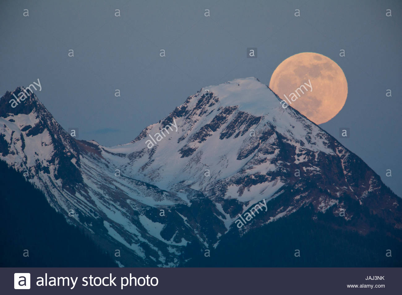 A full moon above the Chugach Mountains. - Stock Image