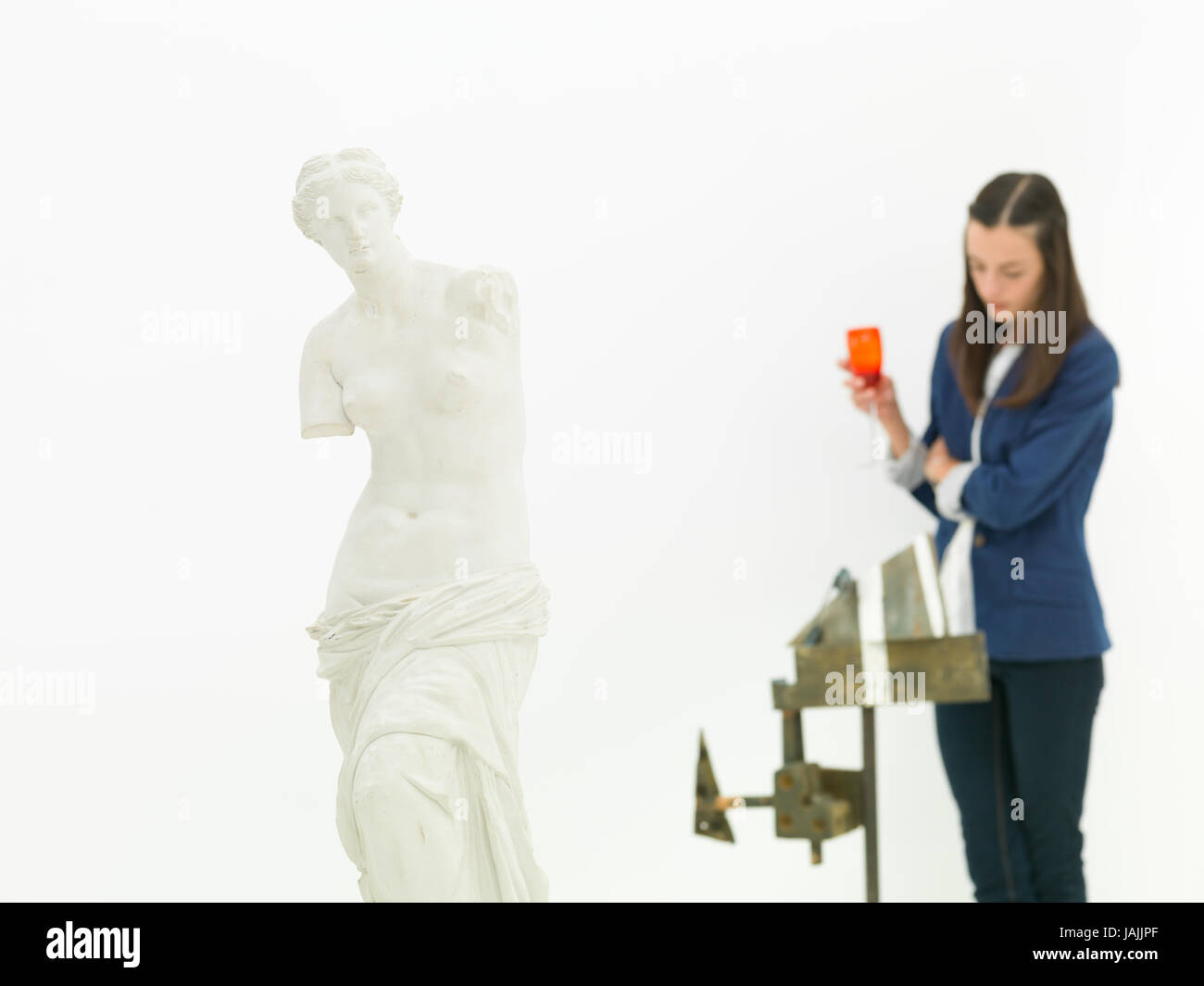 woman scrutinizing sculpture behind a replica of Venus de Milo statue in a museum - Stock Image