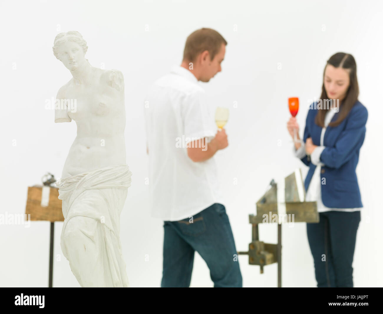woman and man scrutinizing contemporary sculpture behind a replica of Venus de Milo statue in a museum - Stock Image
