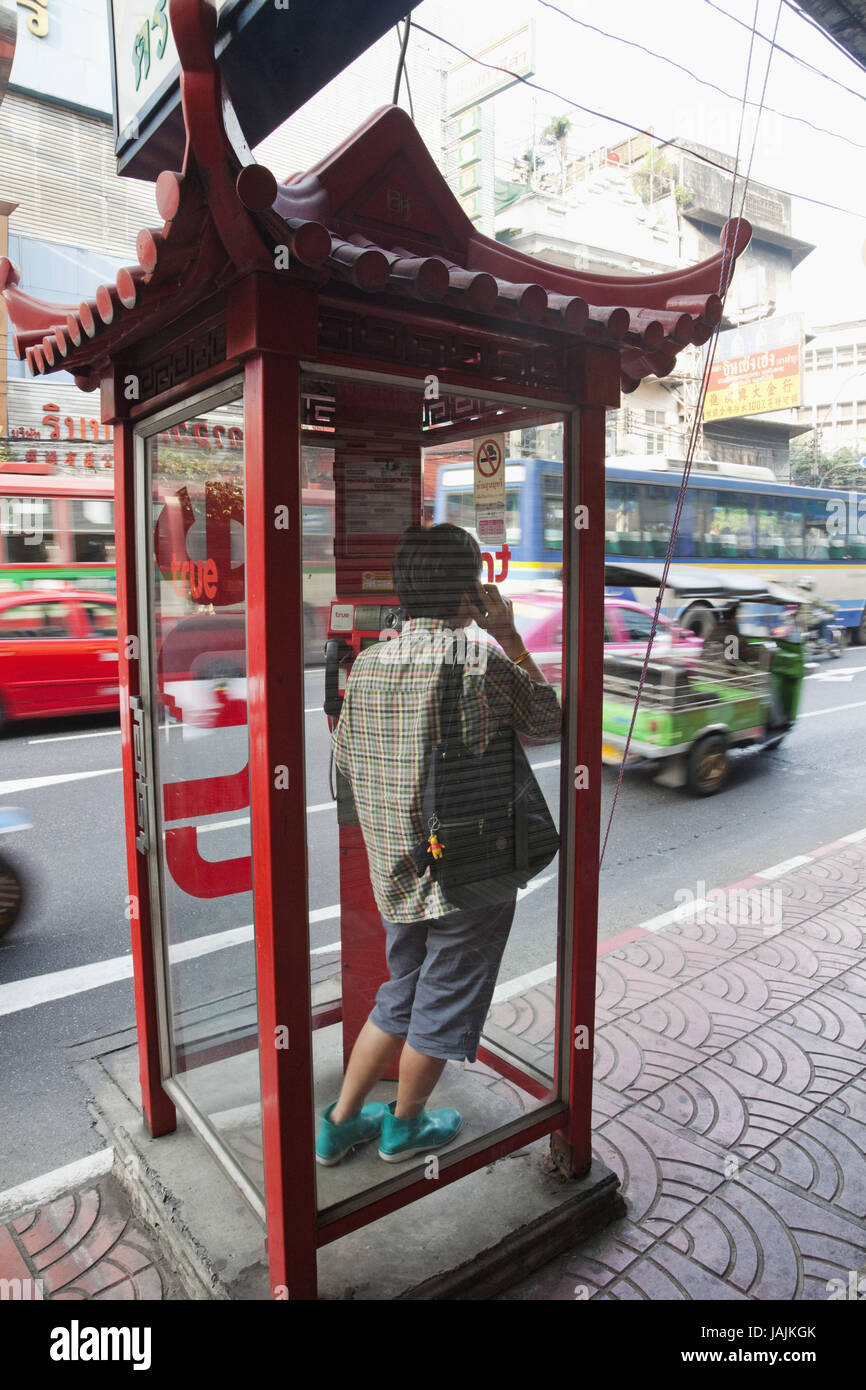To escape Thailand,Bangkok,Chinatown,man with mobile phone in telephone box around traffic noise, - Stock Image